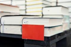 Bokhandelhylla med högen av nya böcker med den röda tomma plattan Nya ankomster på bokhandeln Presentation av boken Copyspace royaltyfria bilder