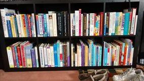 Bokhylla mycket av böcker Arkivbilder