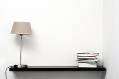 Bokhylla på väggen med lampan och böcker Arkivbild