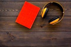 Bokonline-begrepp, audiobooks Spendera leasuretidläsning och lyssnande musik Hörlurar nära inbunden bokboken med Fotografering för Bildbyråer