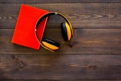 Bokonline-begrepp, audiobooks Spendera leasuretidläsning och lyssnande musik Hörlurar nära inbunden bokboken med Royaltyfria Foton