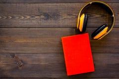 Bokonline-begrepp, audiobooks Spendera leasuretidläsning och lyssnande musik Hörlurar nära inbunden bokboken med Arkivfoto