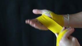 Bokser die de gele verbanden van ` s op zijn hand verpakken vóór strijd stock footage