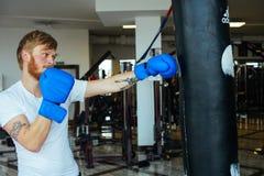 Bokser z uderzać pięścią torbę w gym Obrazy Royalty Free