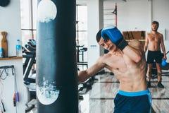 Bokser z uderzać pięścią torbę w gym Fotografia Stock