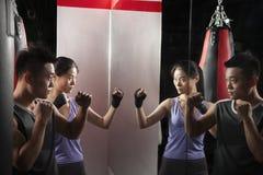 Bokserskiego instruktora i żeńskiego ucznia ćwiczy postawa przed lustrem przy bokserskim gym zdjęcia royalty free