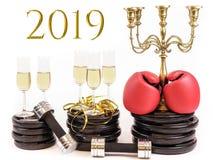 Bokshandschoenen en glazen champagne op gewichtsplaten en domoren Concept voor nieuwe jarenresolutie 2019 en training royalty-vrije stock afbeeldingen