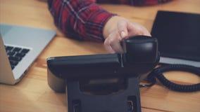 Bokslutet av en kvinnas händer i kontoret med telefonen i hennes händer ligger på tabellen, i arbetsplatsen modernt arkivfilmer