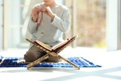 Bokställning med Koranen och litet muslimskt be för pojke arkivbild