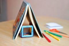 Bokställningarna på en tabell i formen av ett hustak, bildar ett hus med ett märkes- hem- begrepp för ett barn, familj royaltyfria bilder