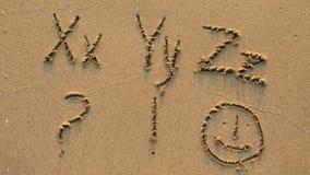 Bokstäver av alfabetet som är skriftligt på den sandiga stranden Royaltyfria Foton
