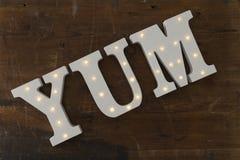bokstäver 3D med upplysta inbäddade LEDDE ljus som stavar YUM Arkivfoto