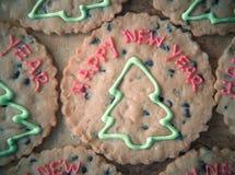 Bokstäver för lyckligt nytt år med julgranar på bruna kakor Royaltyfri Foto