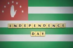 Bokstäver med textsjälvständighetsdagen på nationsflaggan av Abchazien Royaltyfri Fotografi