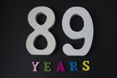 Bokstäver och nummer åttionio gamla år på en svart bakgrund Arkivbild