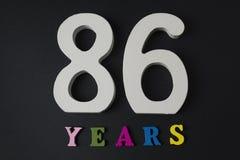 Bokstäver och nummer åttiosex gamla år på en svart bakgrund Royaltyfria Foton