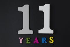 Bokstäver och nummer elva år på den svarta bakgrunden Arkivbild