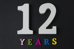 Bokstäver och nummer för tolv år på en svart bakgrund Royaltyfri Fotografi
