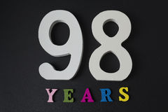 Bokstäver och nummer nittio gamla år på en svart bakgrund Fotografering för Bildbyråer
