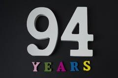 Bokstäver och nummer nittiofyra år på en svart bakgrund Arkivbild