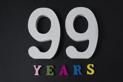 Bokstäver och nummer nittionio år på en svart bakgrund Royaltyfri Bild