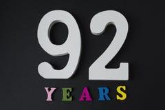 Bokstäver och nummer nittiotvå år på en svart bakgrund Royaltyfri Bild
