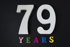 Bokstäver och nummer sjuttionio år på en svart bakgrund Arkivbilder