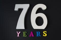 Bokstäver och nummer sjuttiosex år på en svart bakgrund Royaltyfria Bilder