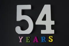 Bokstäver och nummer till femtiofyra på en svart bakgrund Arkivfoto