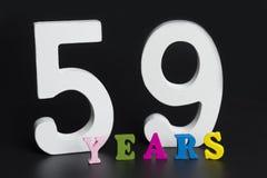 Bokstäver och nummer till femtionio på en svart bakgrund Arkivfoton