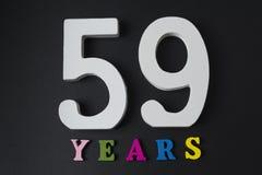 Bokstäver och nummer till femtionio på en svart bakgrund Royaltyfria Foton