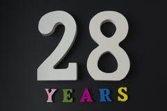 Bokstäver och nummer tjugoåtta år på en svart bakgrund Arkivfoto