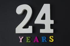 Bokstäver och nummer tjugofyra år på en svart bakgrund Arkivbild
