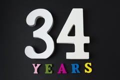 Bokstäver och nummer trettiofyra år på en svart bakgrund Arkivbilder