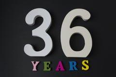 Bokstäver och nummer trettiosex år på en svart bakgrund Arkivfoton