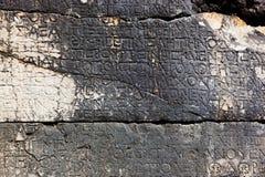 Bokstäver på stenen i Phaselis, Turkiet Royaltyfri Foto