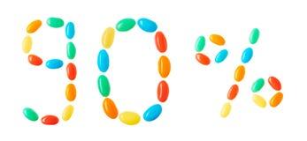 90% bokstäver som göras av isolerade mångfärgade godisar på vit Arkivfoton