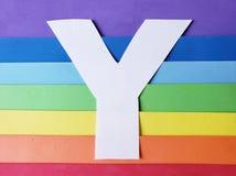 bokstav E i vit med bakgrund i regnbåge färgar arkivfoto