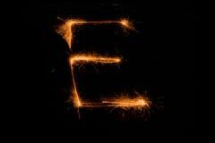 Bokstav E som göras av tomtebloss på svart Royaltyfri Fotografi
