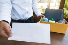 Bokstav för anställdinnehavavsägelse och inpackning av en ask för att lämna kontoret arkivfoton