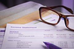 Bokstav för inkomstmeddelande på det bruna kuvertet och monokeln, penna, bu Royaltyfri Bild