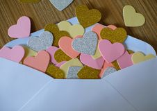 Bokstav för valentindagförälskelse Det öppnade kuvertet och många klädde med filt hjärtor royaltyfria foton