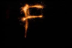 Bokstav F som göras av tomtebloss på svart Arkivfoton