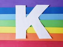 bokstav K i vit med bakgrund i regnbåge färgar arkivfoto