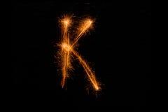 Bokstav K som göras av tomtebloss på svart Royaltyfri Fotografi
