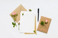 Bokstav, kuvert och gåva på vit bakgrund Inbjudankort eller förälskelsebokstav med rosa rosor Semestra begreppet, bästa sikt, pla Arkivbilder