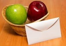Bokstav mot äpplen i en korg Arkivfoton