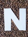 bokstav N i vit och bakgrund med grillade kaffebönor, bakgrund och textur arkivbild