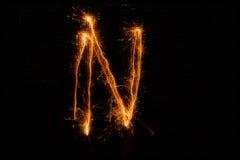 Bokstav N som göras av tomtebloss på svart Arkivbild