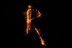 Bokstav R som göras av tomtebloss på svart Royaltyfri Foto